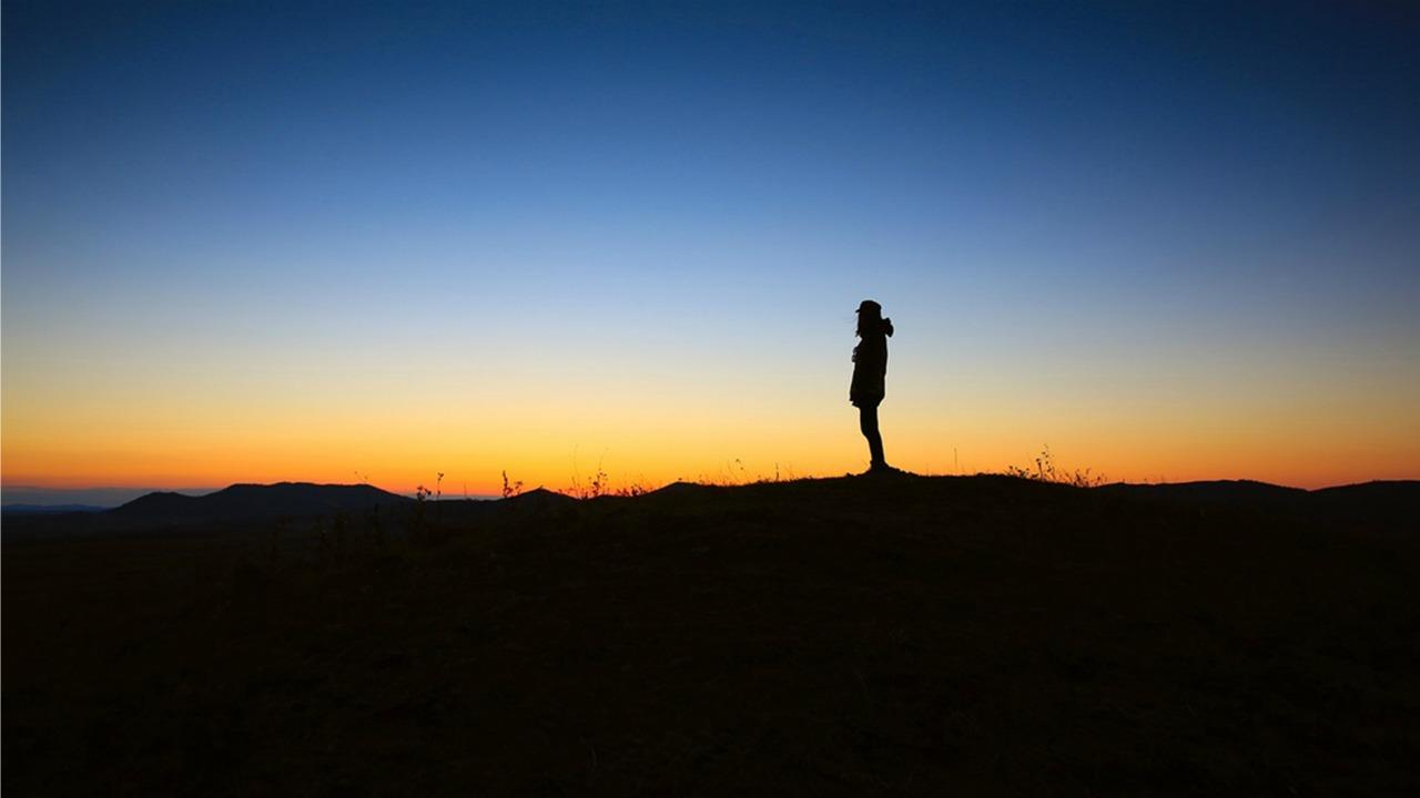 человек стоит одиноко на фоне заката